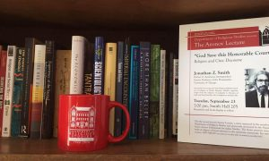 photo of a mug and books on a shelf